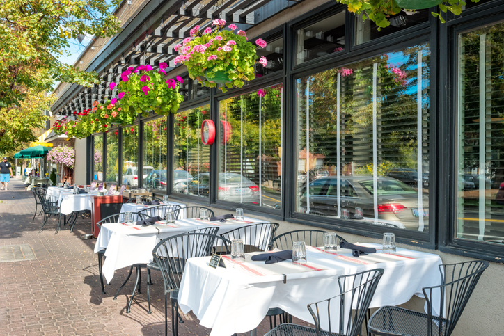 Restaurant patio filled with lush greeneries setup for outdoor dining