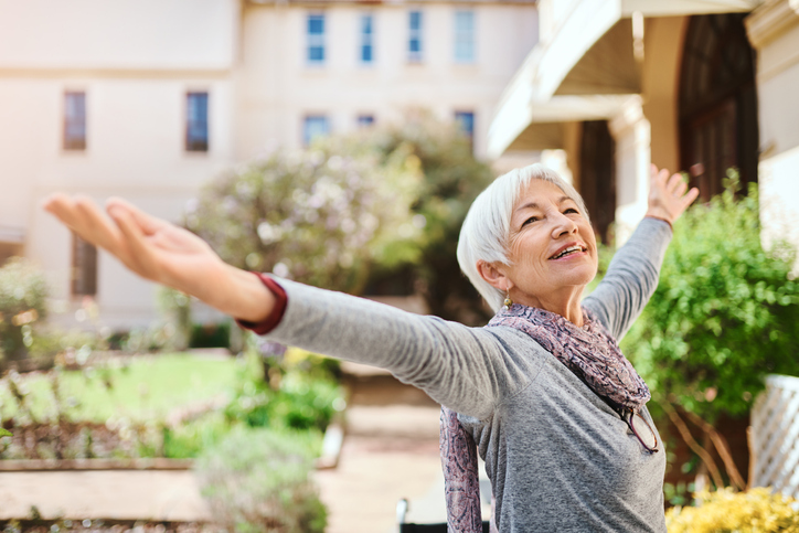 Senior Woman Smiling and Looking Up While Raising Her Hands in the Air