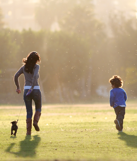 Woman holding a puppy while playing with a kid in the field
