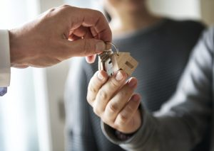 family holding their key to their new home