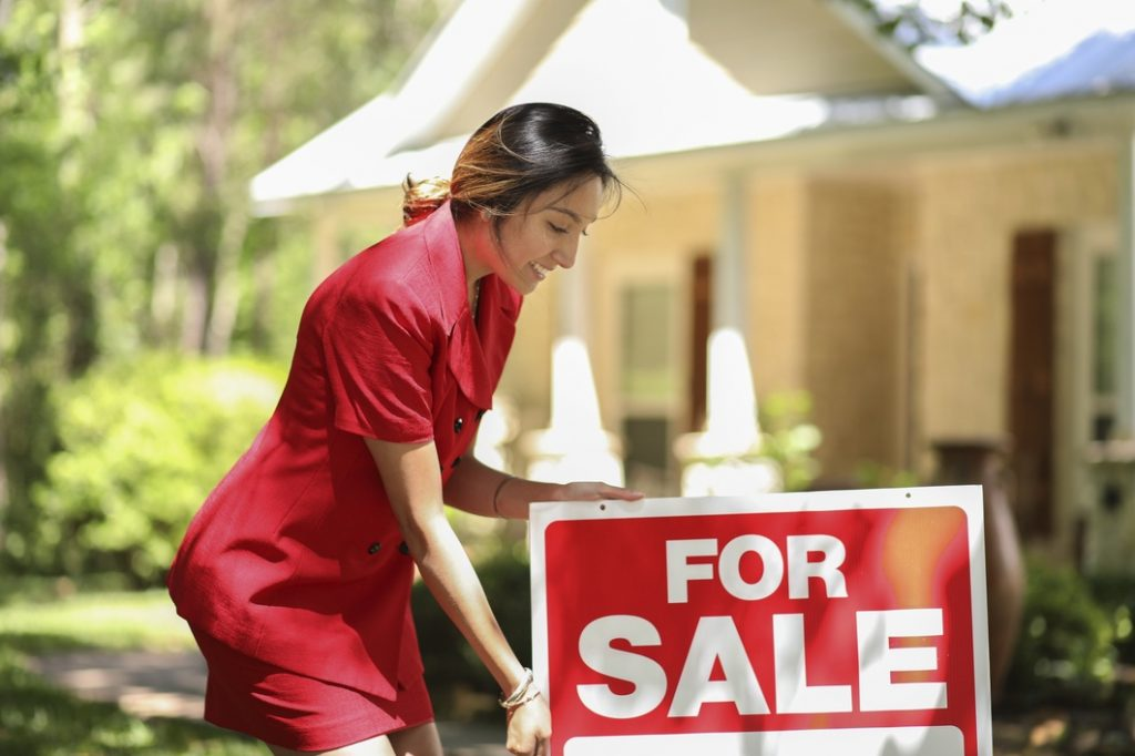 Woman putting a For Sale sign in front of a house