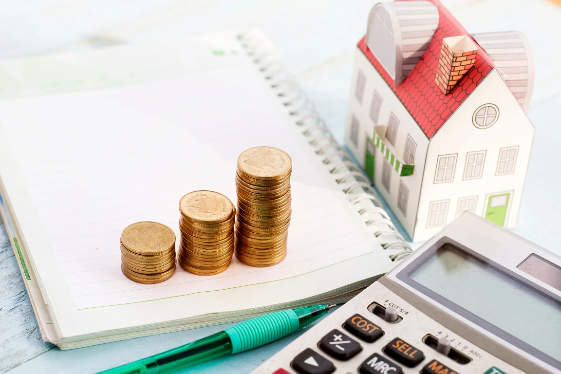 Notebook, calculator, miniature home model, and coins placed on a table