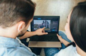 couple choosing new house using laptop